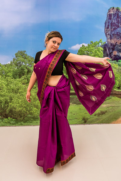 This is a photo of Maria wearing a traditional Sri lankan sari. She is posing in front of a huge Sigiriya poster at a silk products showroom in Sigiriya.
