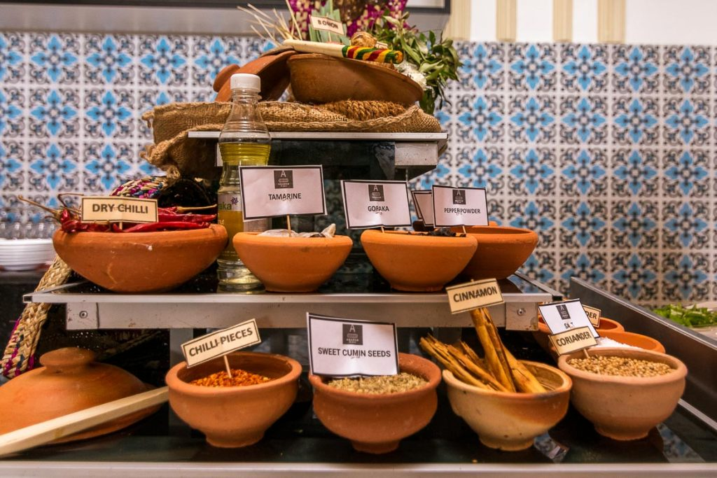 This photo shows many bowls filled with Sri Lankan spices. Each bowl has a label with the spice's name on it.