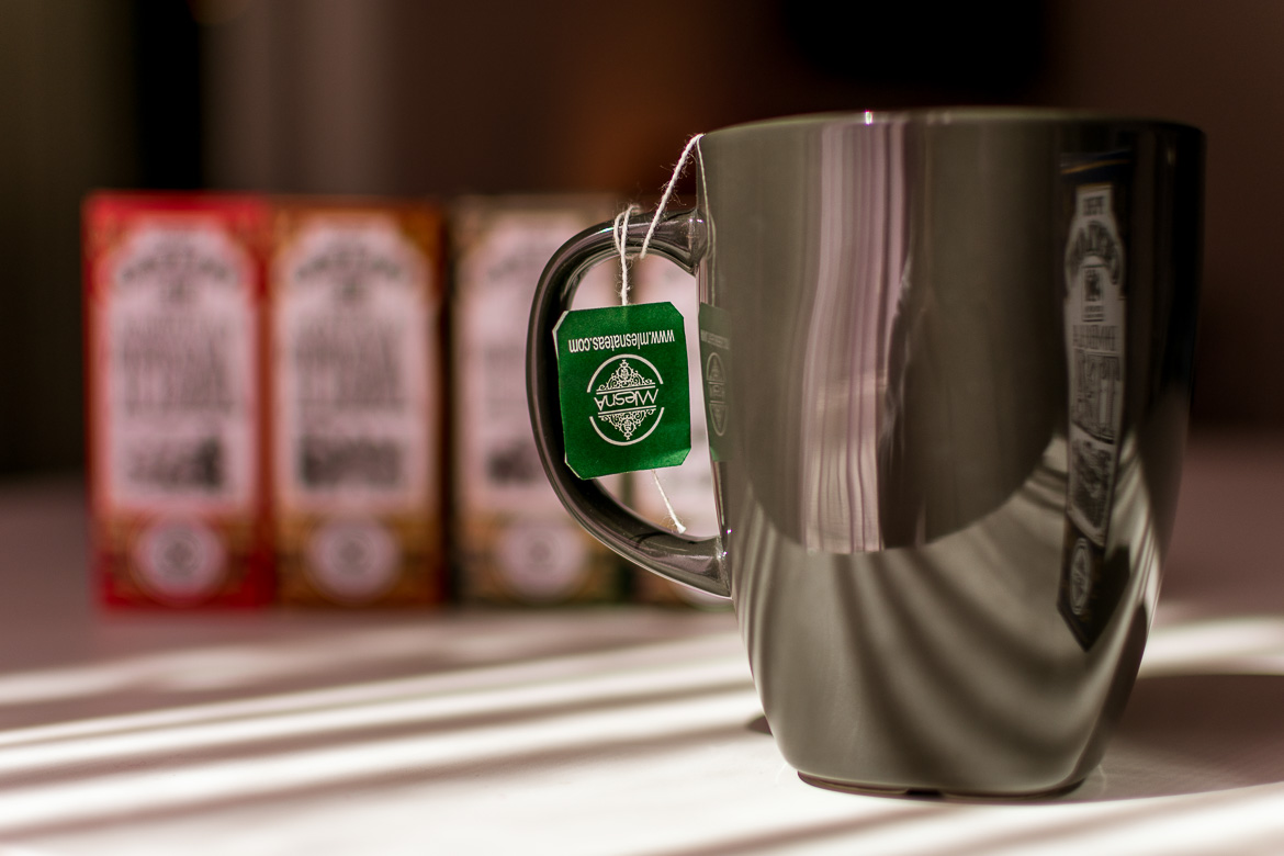 This is a close up of a cup of Sri Lankan tea. In the background various packages of Ceylon tea.