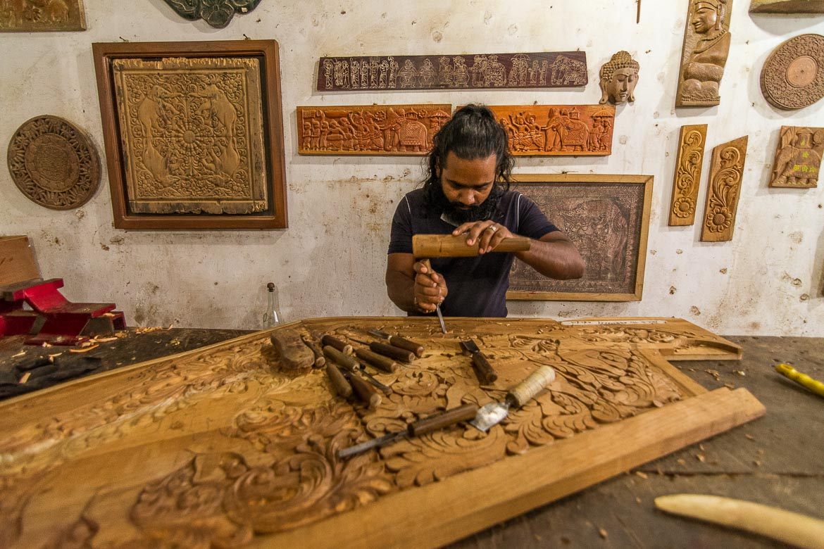 This photo was shot inside a wood workshop in Kandy. The man is carving elaborate designs on a huge piece of wood.