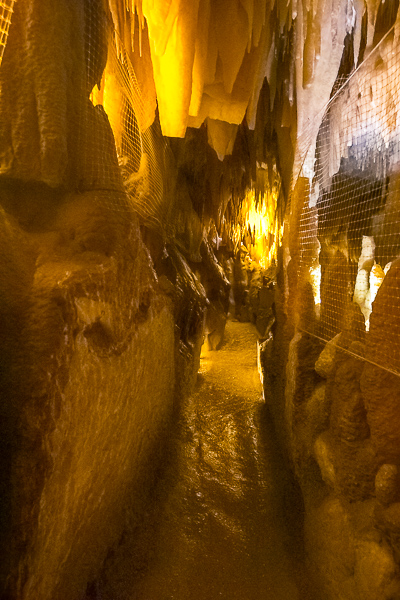 This image shows a narrow corridor with stalactites in Castellana Caves.
