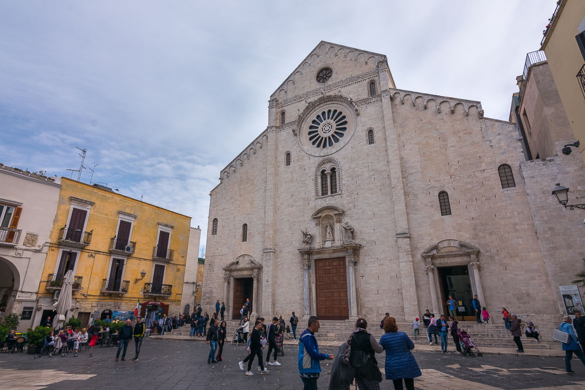 This photo shows the facade of San Sabino Cathedral at Odegitria Square in Bari. There are many people walking around the square or sitting at the church's steps.