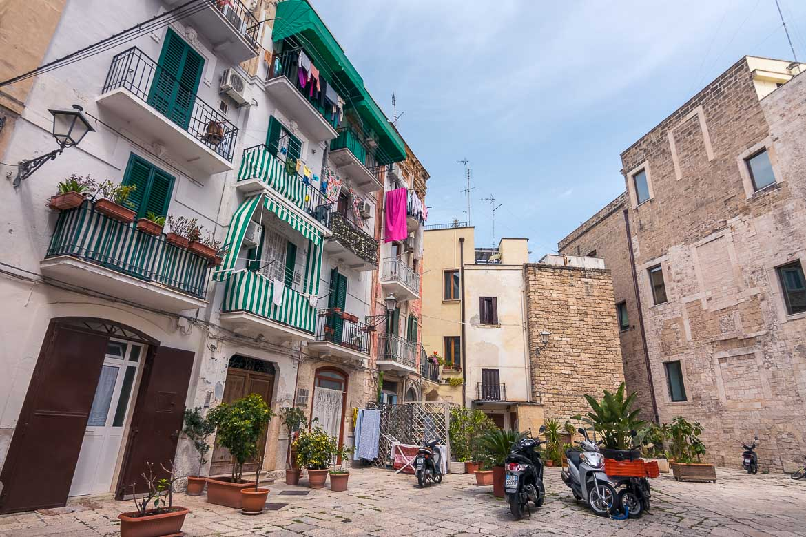This photo shows an open space in Bari Old Town. There are buildings around it and some scooters parked next to pots of plants.