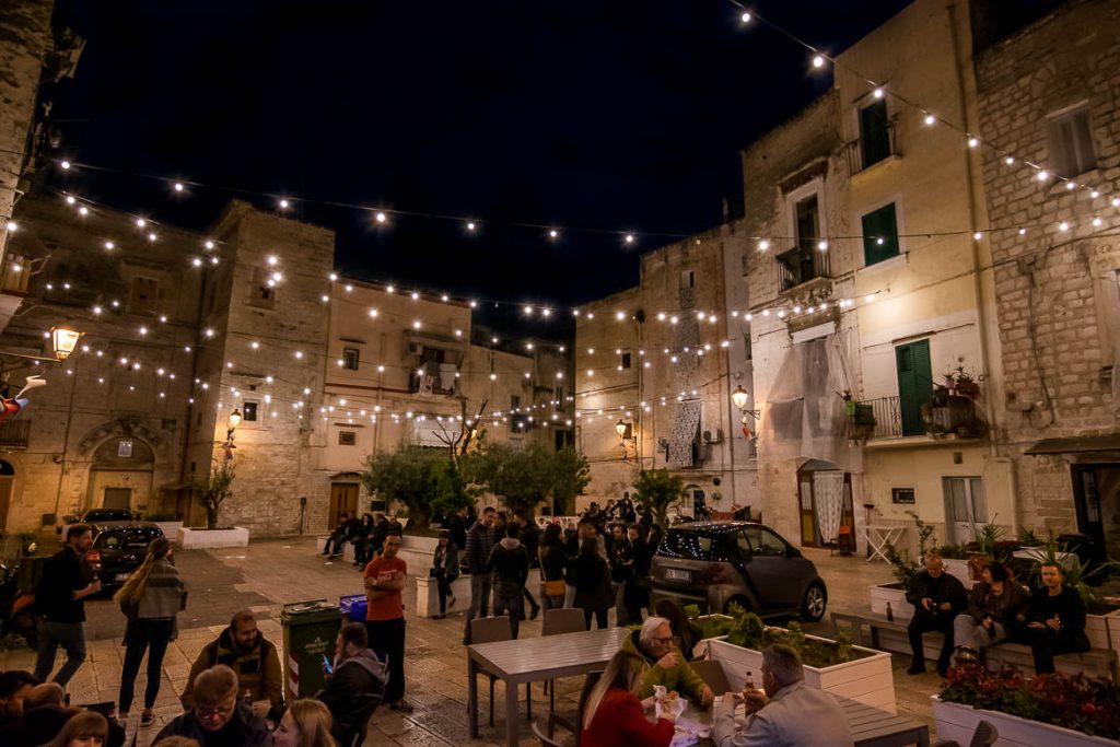 This image shows Largo Albicocca at night. There are people standing or sitting and there are lines of lights hanging above. The ambience is unique. This is why we chose this photo to be the feature image of our article: What to do in Bari Italy. A full guide to Puglia's capital.