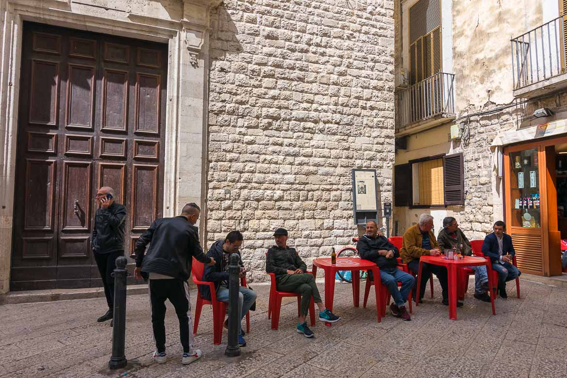 This image shows men sitting and chatting on plastic chairs and tables on one of the main pedestrianised streets in Bari Vecchia. This isn't at all uncommon and it adds to Bari's overall charm.