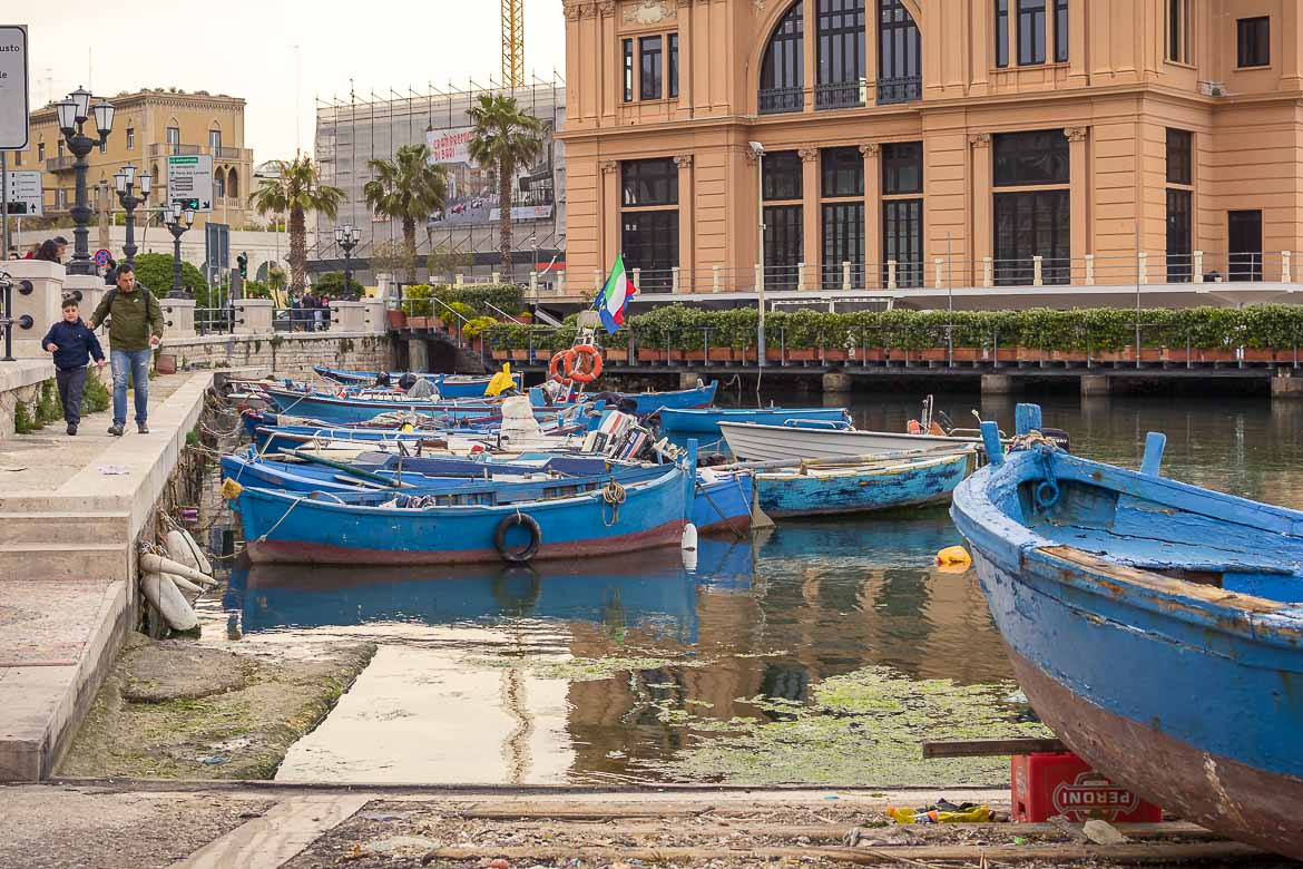 This image shows the iconic blue fishing boats in the Old Port of Bari. In the background, the beautiful Teatro Margherita.
