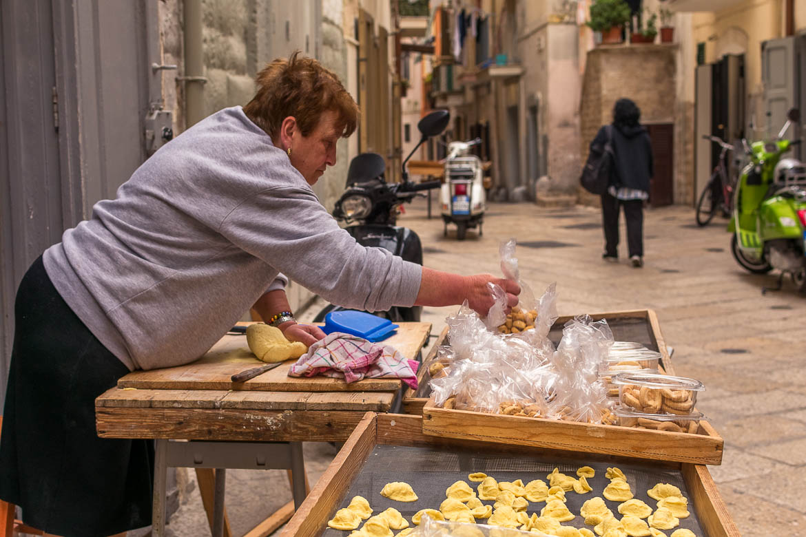 This image shows a local lady making pasta and other treats in Orecchiette Street.