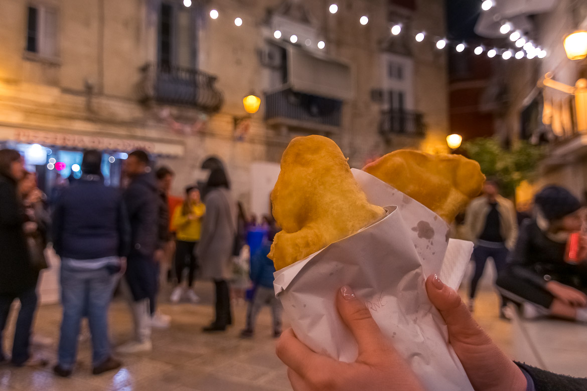 This is a close up of Maria's hands holding two delicious panzerotti. In the background, there are many people standing outside the Pizzeria di Cosimo.