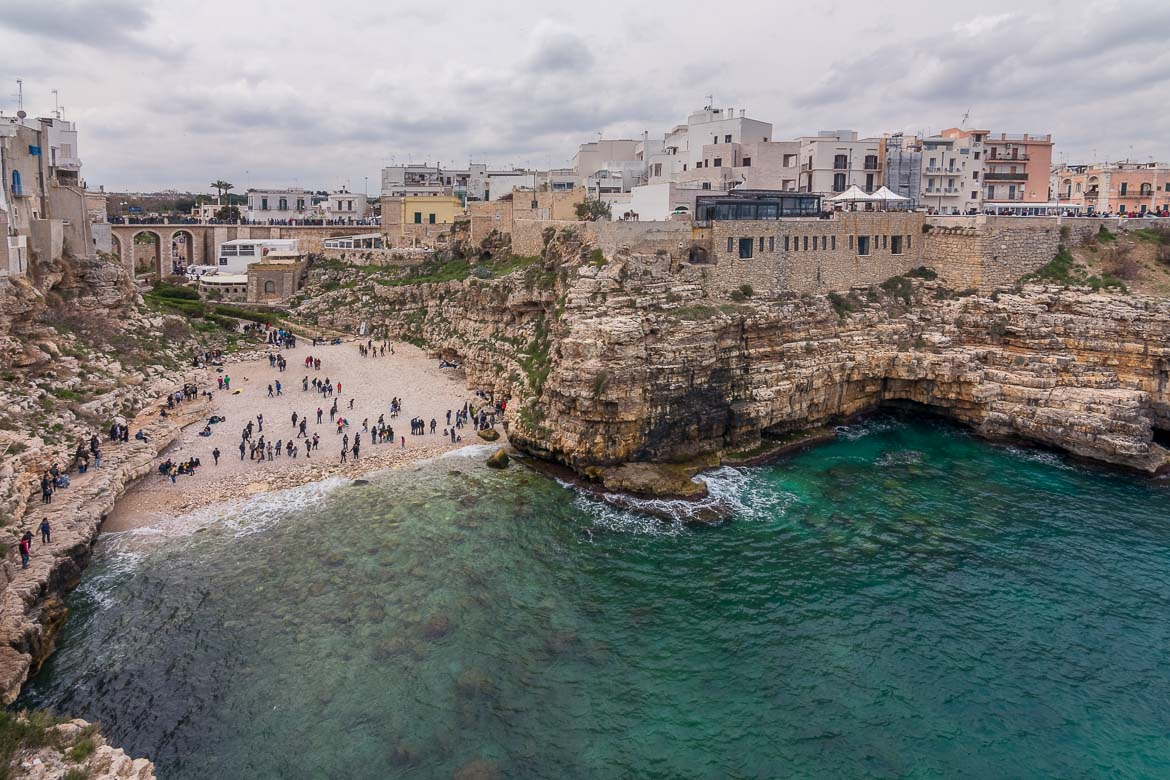 This is a panoramic view of Polignano a Mare as seen from the Terrazza Santo Stefano. It is a cloudy day and there are some people hanging out on the beach.