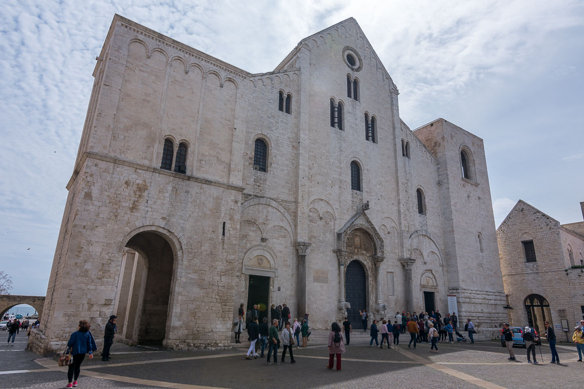 This is a photo of the facade of Basilica San Nicola. The latter is perhaps the city's most important church. There are quite a few people outside the church.