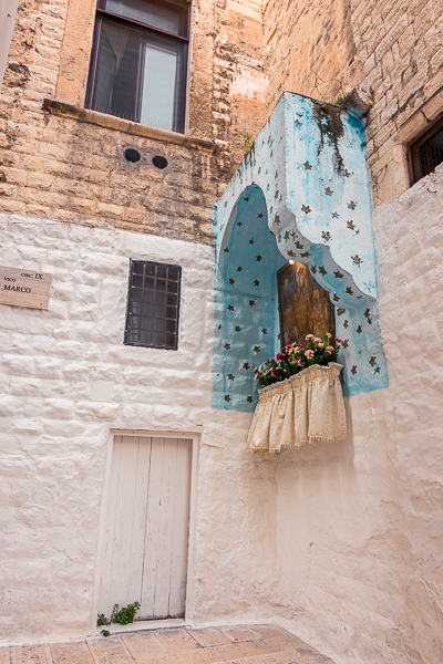 This image shows a beatiful shrine on a wall in Bari Old Town. It is painted in sky blue and it's decorated with fresh flowers.