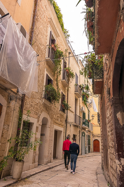 This is an image of a narrow alley in Bari Old Town. There are two men walking and there are balconies filled with plants and flowers above them. If you're wondering what to do in Bari, you should definitely walk around Bari Old Town.