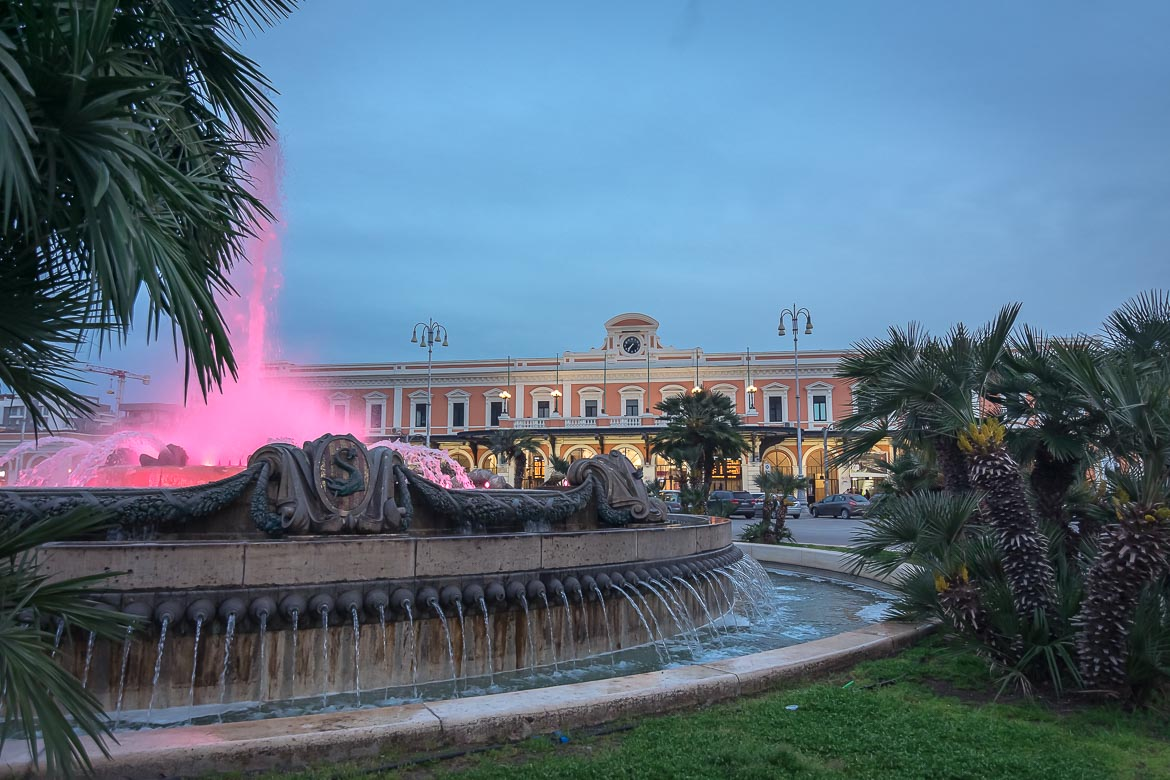 This photo shows a splendid fountain lit up in bright pink in the foreground. In the background, the building of Bari Centrale, the main railway station in the city.