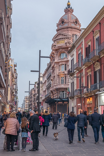 This image shows Via Sparano da Bari in the evening. The street is full of people. In the background, the gorgeous Palazzo Mincuzzi.
