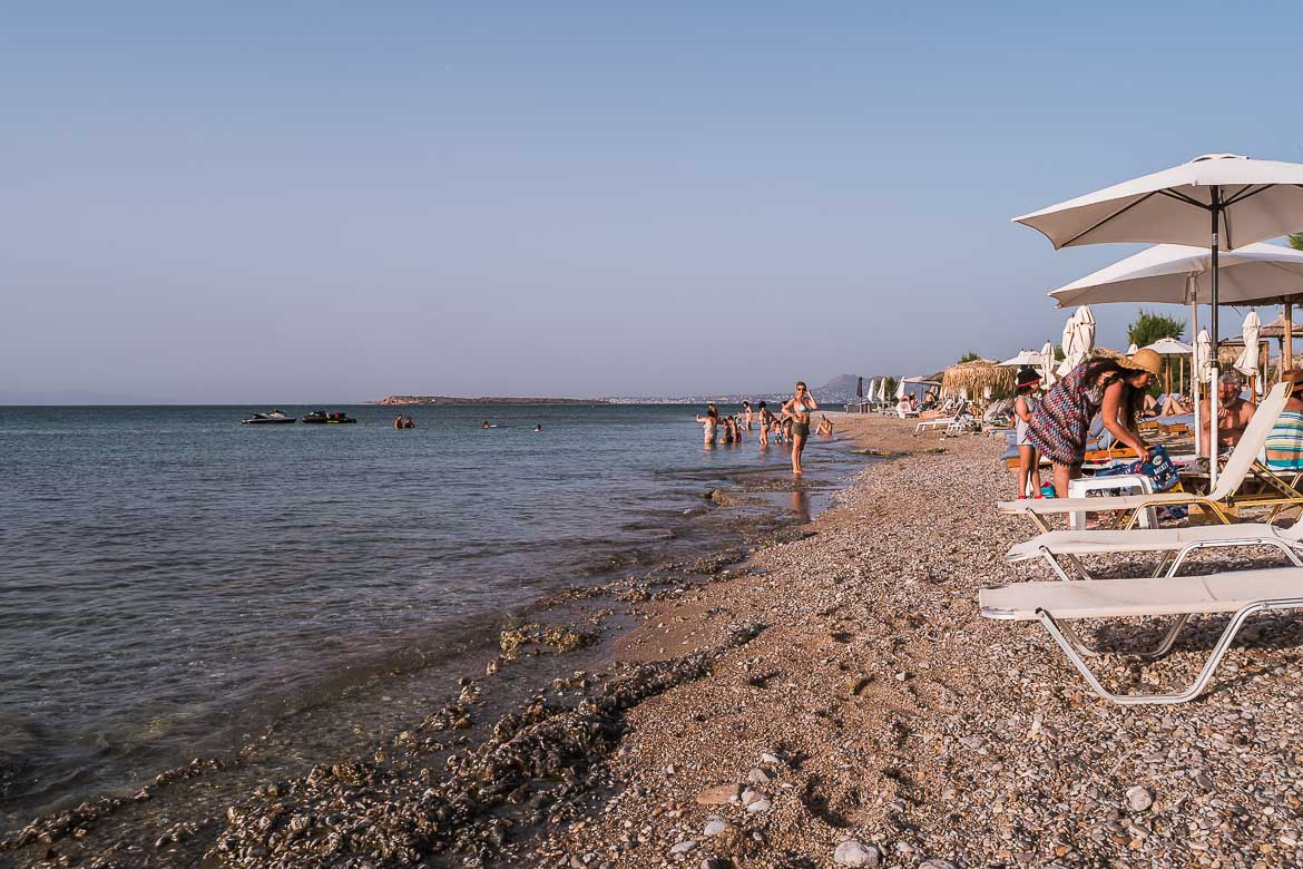 This image shows sunbeds at the edge of the shore on Skala Beach. If you're wondering what to do in Agistri, chilling by the sea is not to be missed!