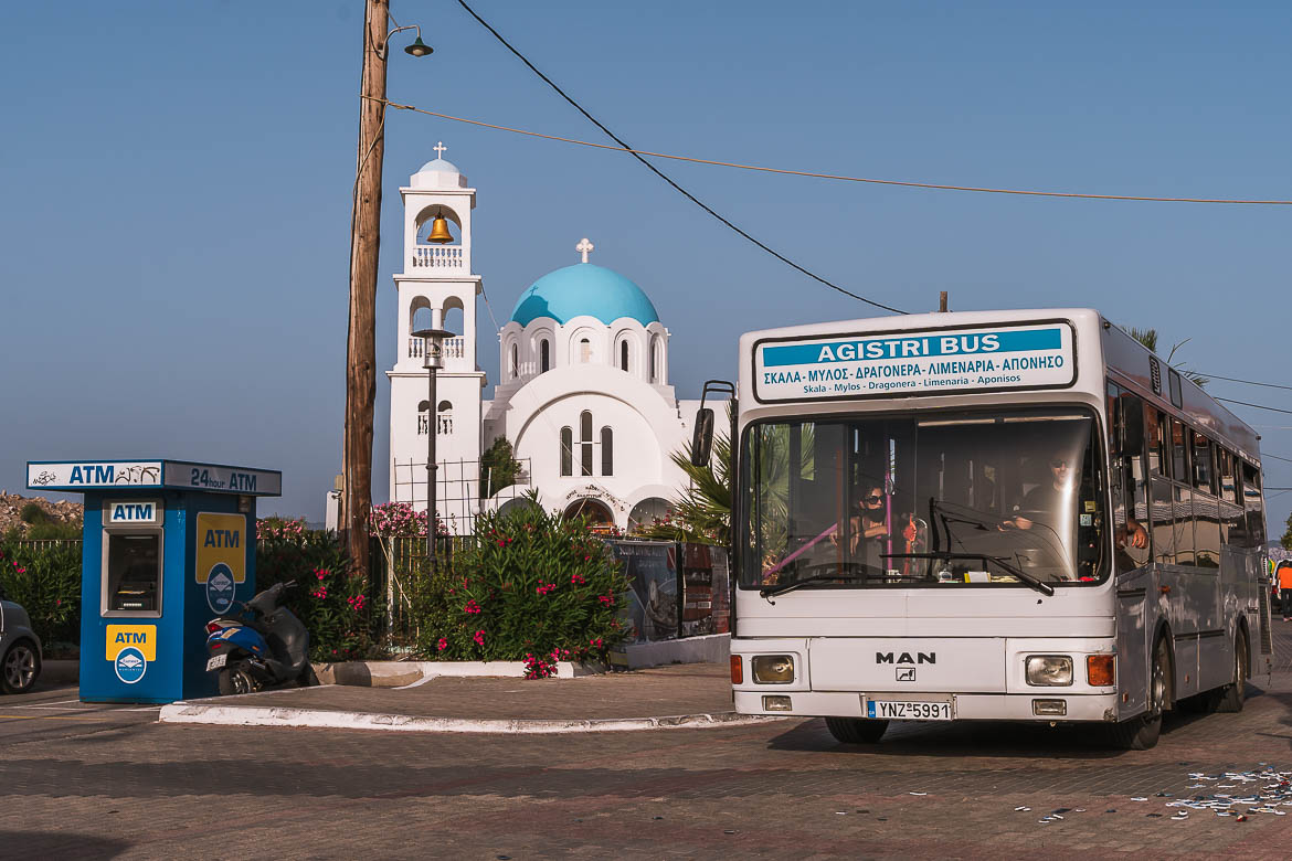 This image shows the public bus of the island as it passes in front of Agioi Anargiroi Church.