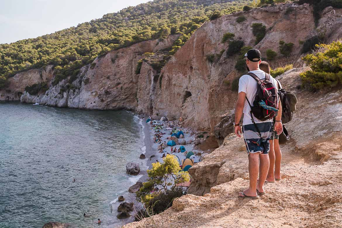 This image shows two people looking at Chalikiada Beach from above. The beach is filled with tents and it's indicative of the Agistri free camping reality.