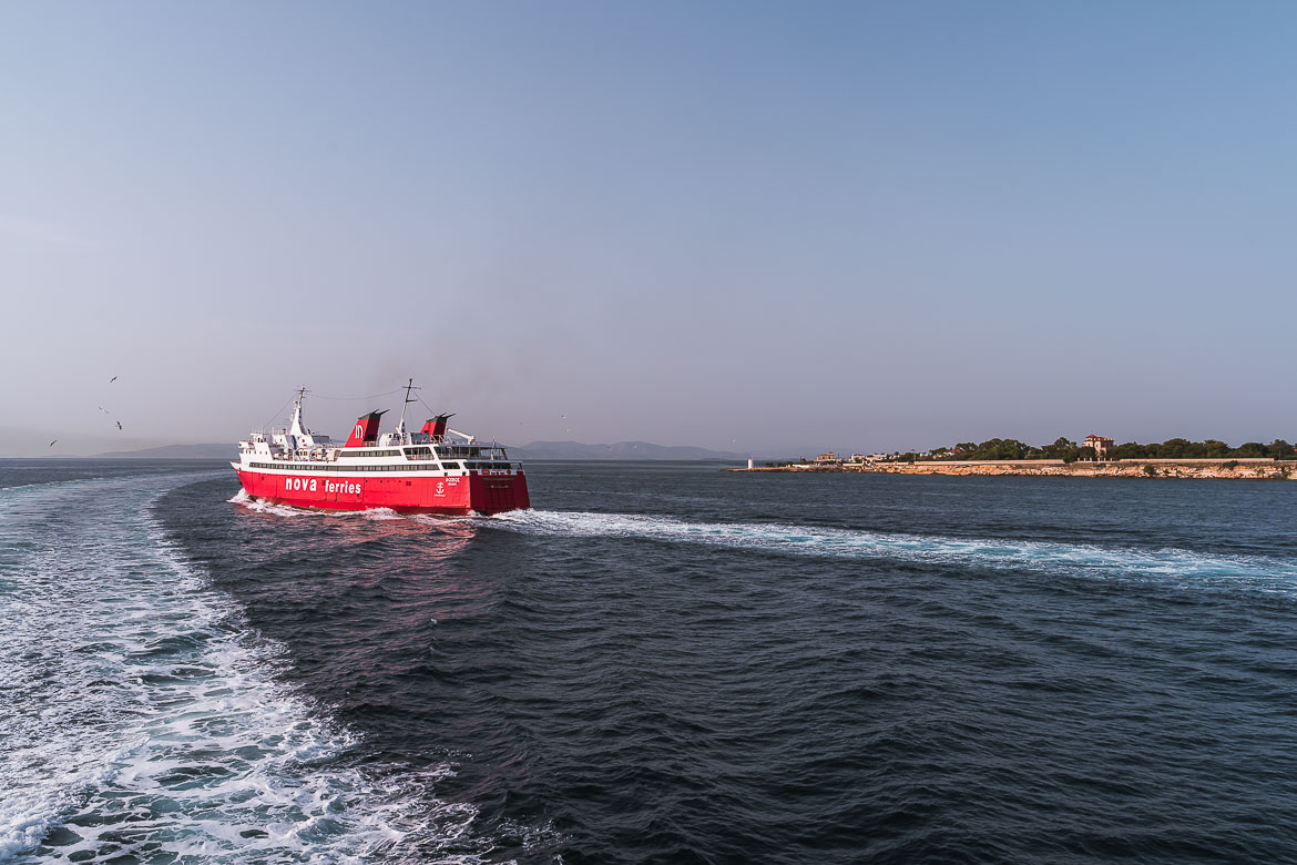 This image shows a red ferry as it leaves the port of Aegina. There are frequent ferries from Piraeus to Agistri.