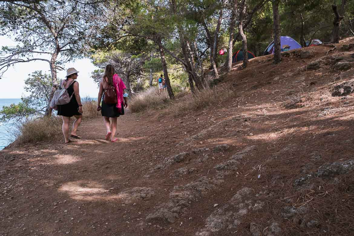 This image shows two girls walking along the path that leads to Chalikiada Beach. There are some tents in the background.