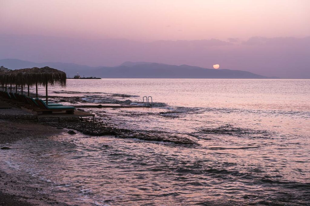 This image shows the sea on Skala Beach dyed purple and the sun setting in the background. This is the featured image for our article What to do in Agistri, the best island near Athens.