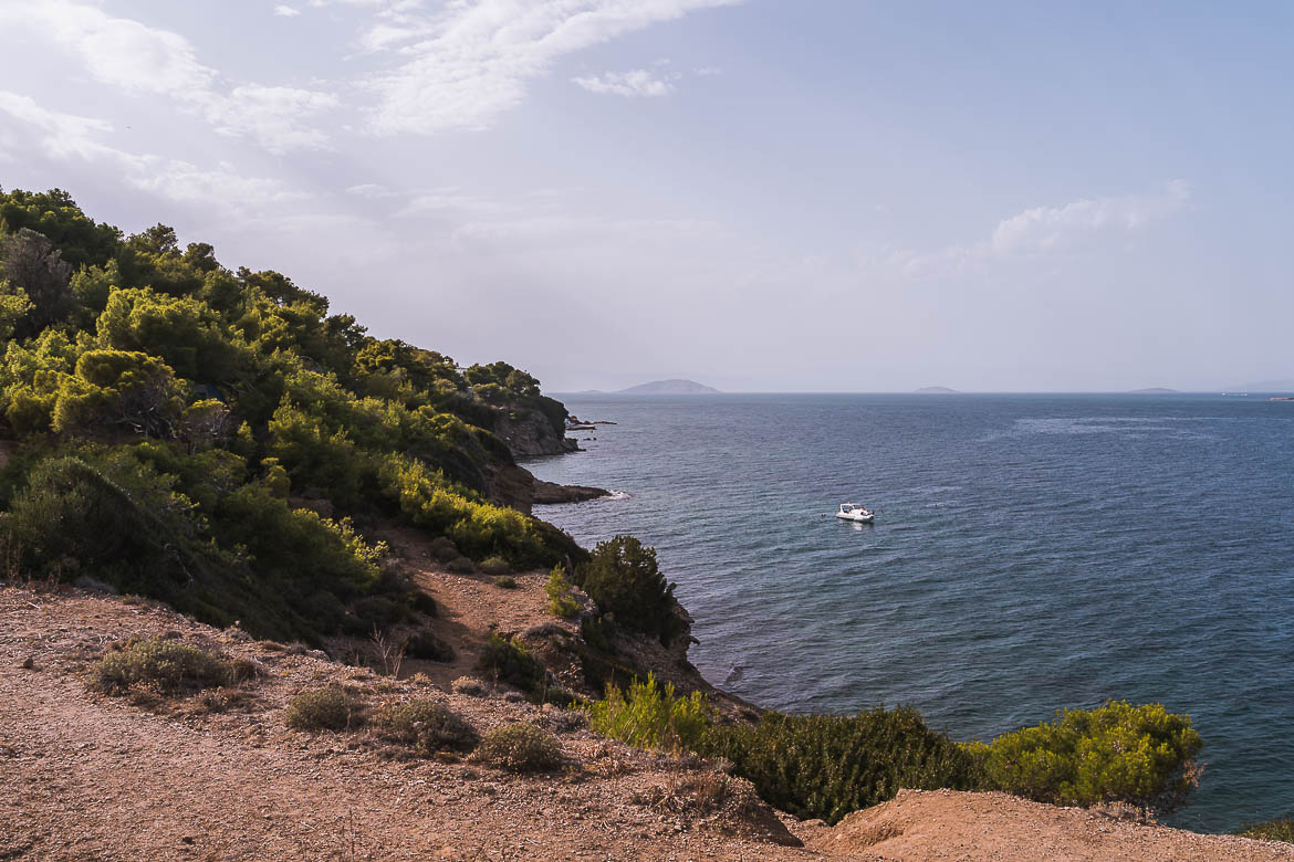 This image shows a green slope and a hiking path with views of the sea. Walking is one of the best things to do in Agistri.