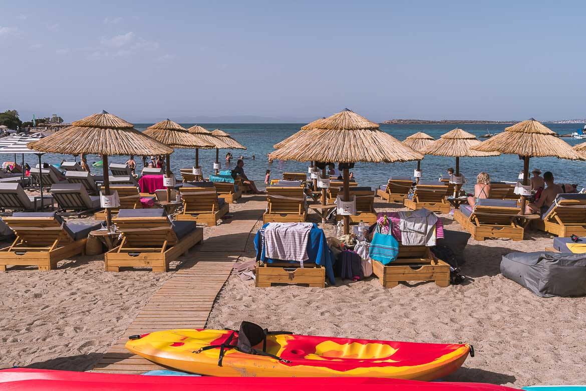 This image shows sandy Skala Beach with straw umbrellas and wooden sunbeds. In the foreground, a couple of canoes on the sand. Water sports are the most popular activities in Agistri.