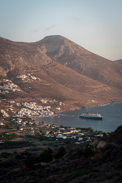 This is a panoramic shot of Aegiali Port as seen from Tholaria Village. There's a ferry that just left the port behind.