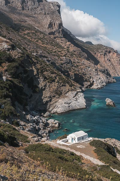 If you're wondering what to do in Amorgos Greece, Agia Anna Bay has crystal clear turquoise waters and gorgeous natural scenery complete with a whitewashed church. This panoramic shot shows all this.
