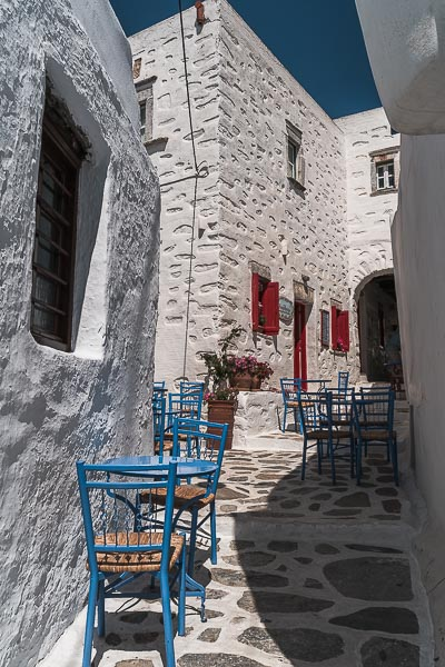 This image shows the whitewashed alley where Kallisto is located. There are blue chairs and tables and red shutters. It's utterly picturesque!