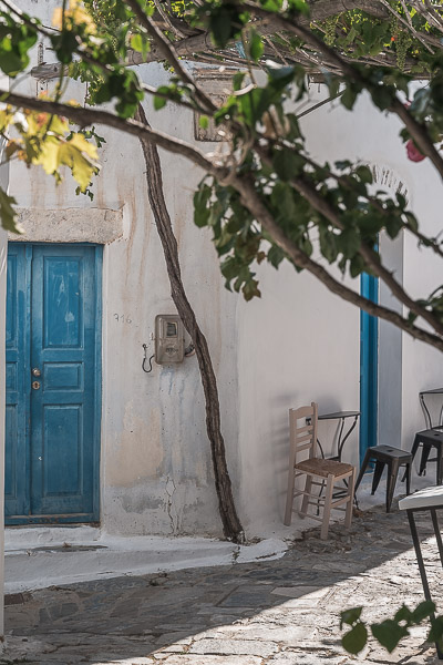 This image shows sime chairs resting against the whitewashed wall next to a blue door.