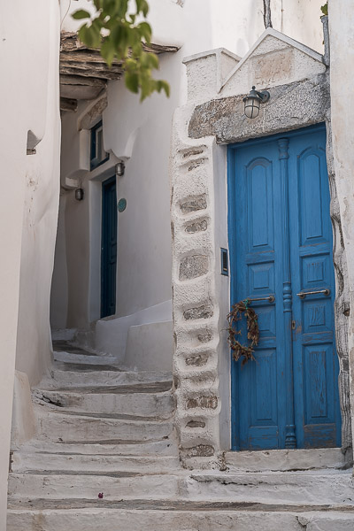 This is a close up of a blue door and whitewashed steps.