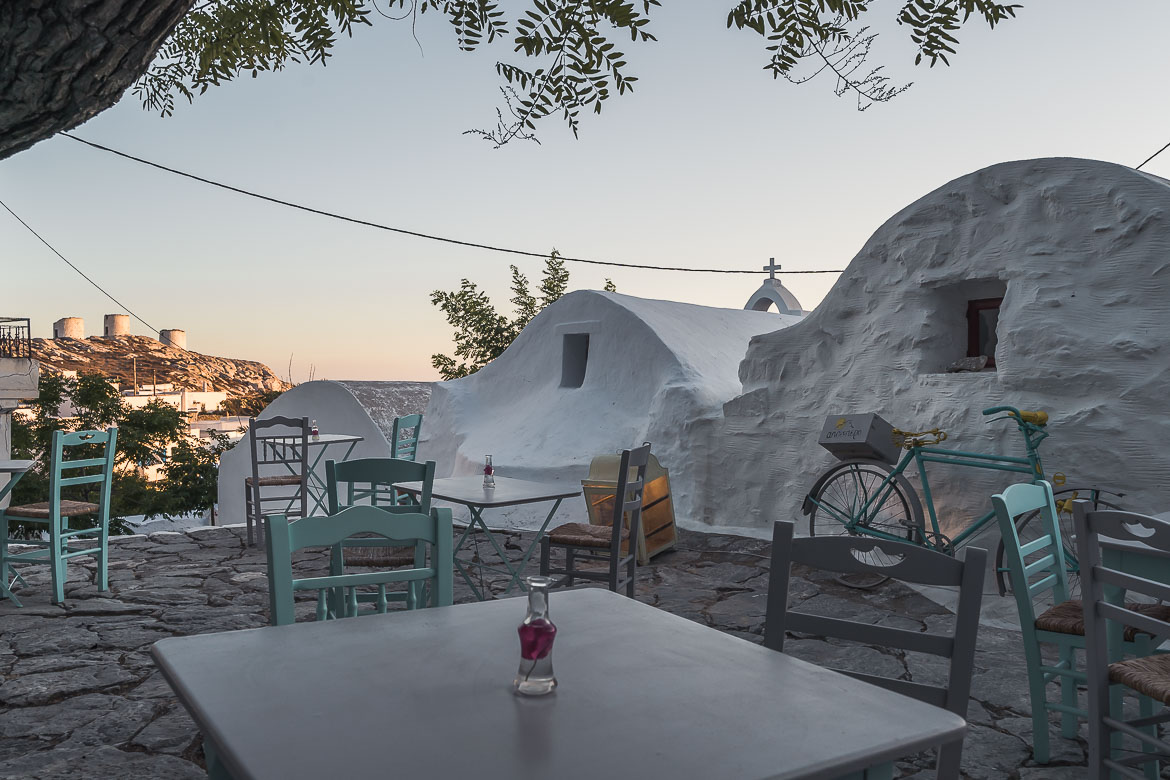 This image shows tables and chairs set at a small square in the heart of Chora Amorgos. The windmills are visible in the background.
