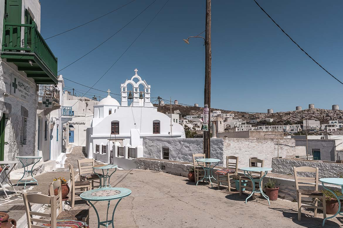 This image shows the entrance to Chora, the old town of Amorgos. There is a church dominating the photo and traditional tables and chairs lining the street.