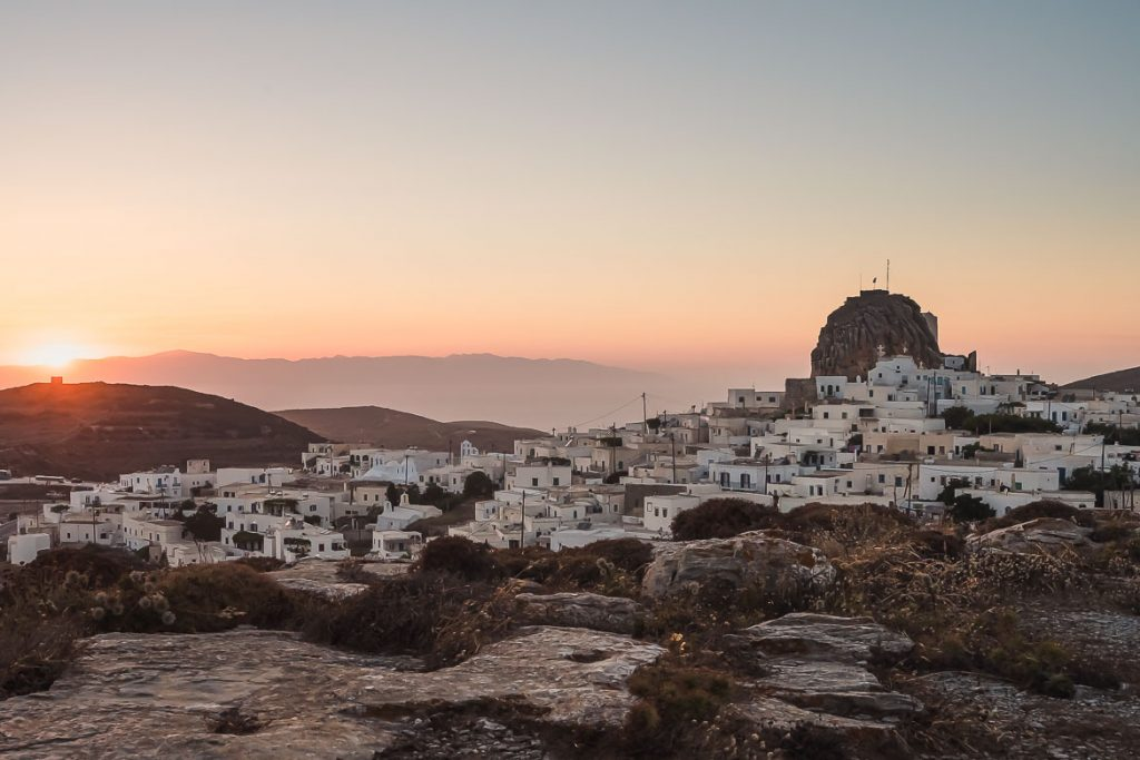 This is a panoramic shot of Chora at sunset, taken from the windmills. The sky is orange and the buildings are whitewashed. You can see the sea in the background. This is the featured image for our article: What to do in Amorgos Greece.