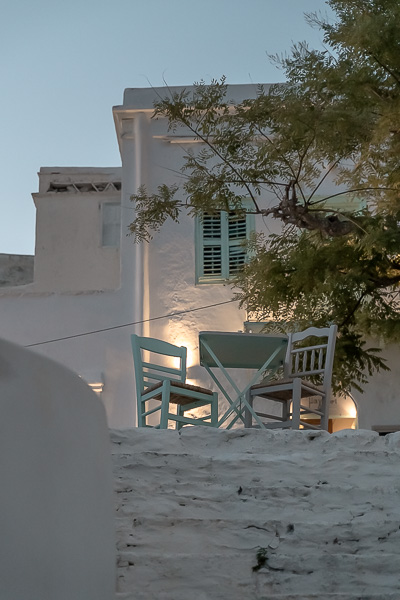 This image shows a romantic setting in Chora at sunset. A table is set at a gorgeous square.