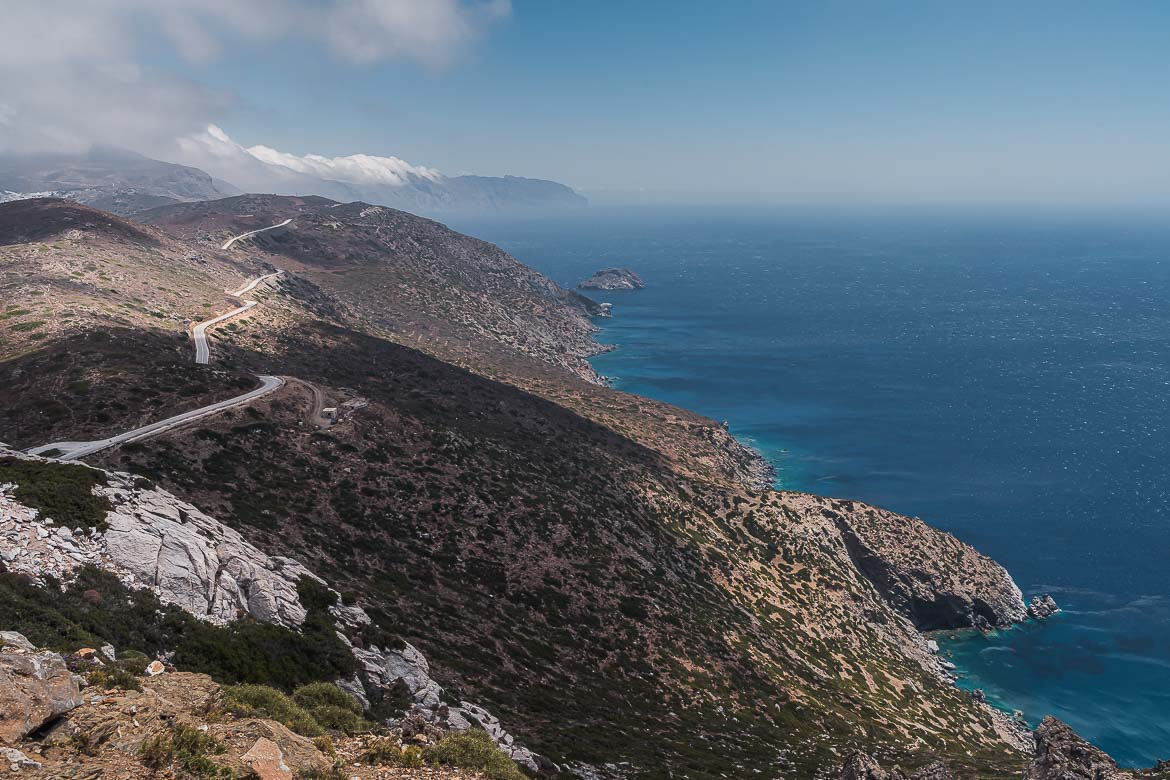 This image shows the winding road at the top of a dramatic cliff and the endless blue sea beyond.