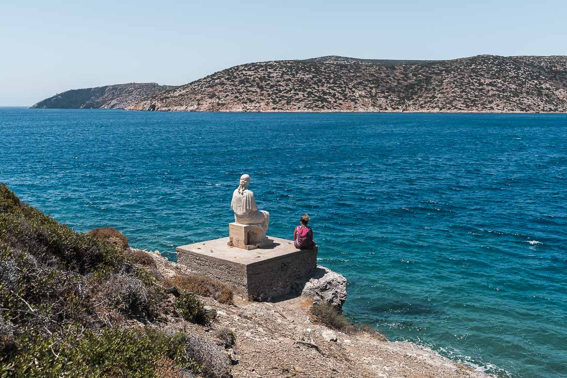 This image shows the back of the statue of Erato as it faces the sea beyond. Maria is sitting next to the statue also gazing at the sea.