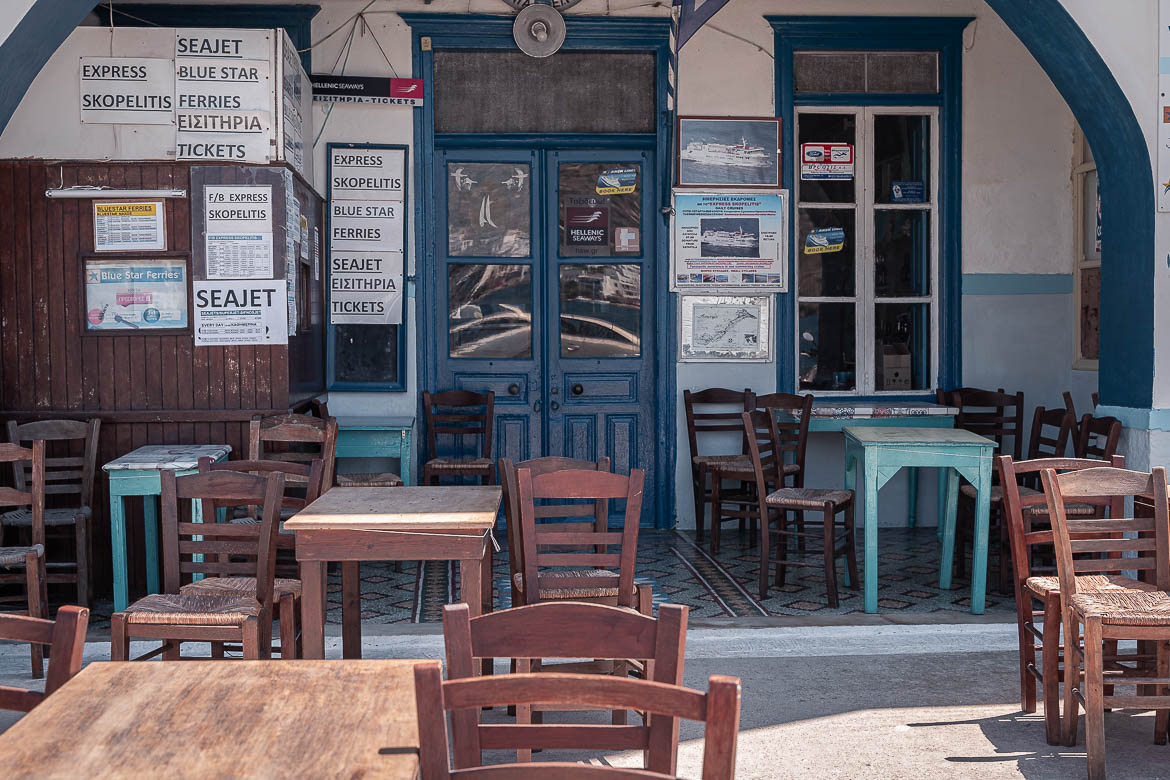 This image shows chairs and tables outside a ferry agency at Katapola.