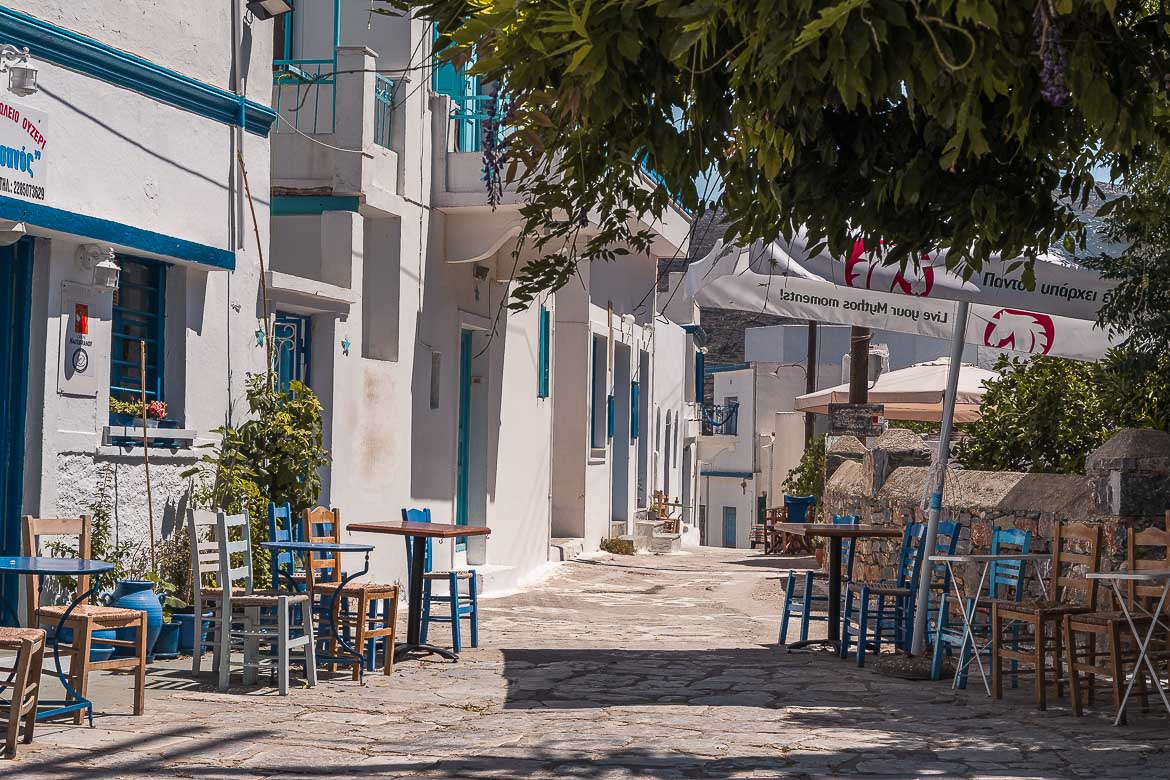 This image shows a cobbled street lined with whitewashed buildings and chairs and tables from two nearby cafes.