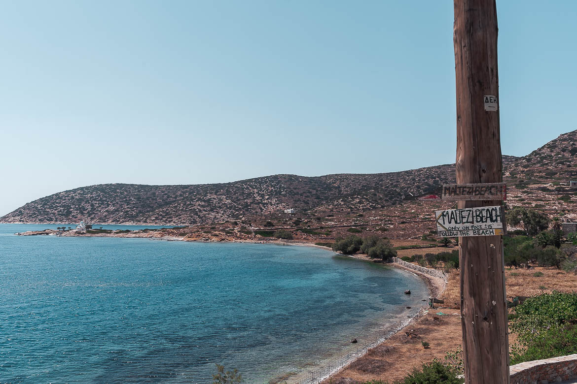 This image shows the sign for the path that leads to Maltezi beach. In the background, the sea is visible.