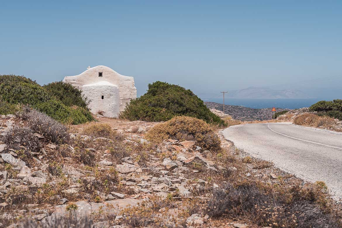 This image shows a secluded whitewashed church at the side of the road.