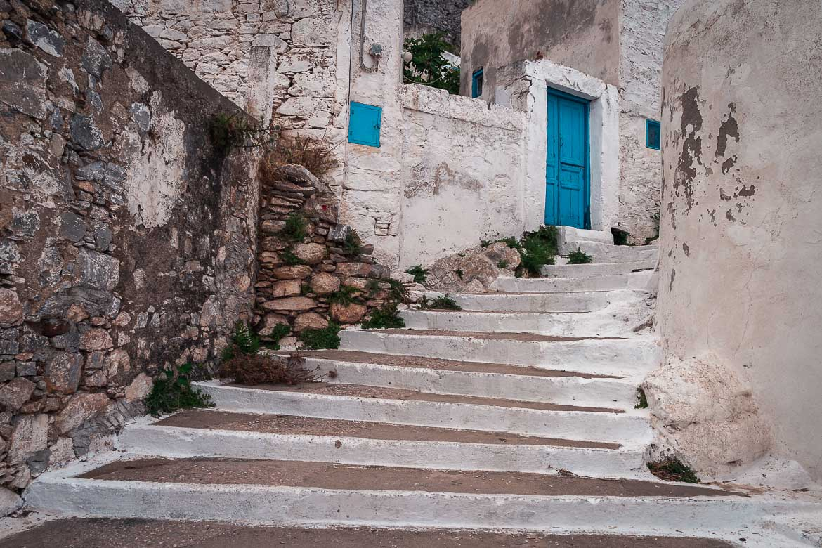This image shows a set of whitewashed steps leading to a blue door.