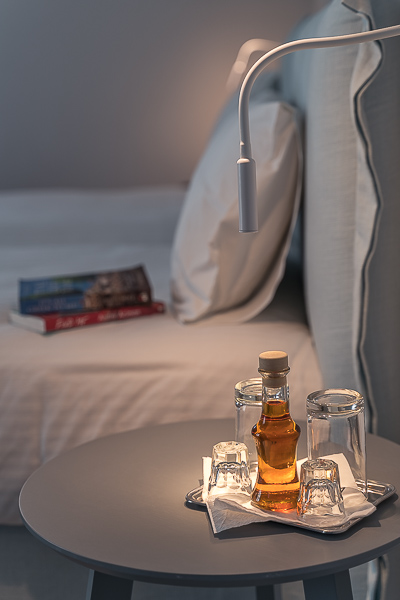 This image shows the interior of our room at Vigla Hotel Amorgos. In the foreground, a bottle of psimeni raki with two shot glasses. In the background, a bed with two books on it.