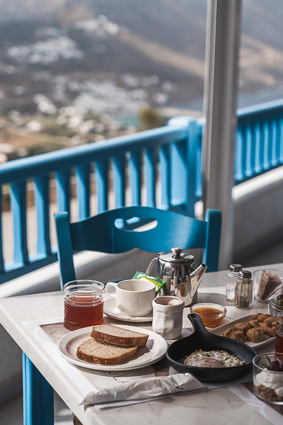 This is a close up of a table set for breakfast. In the background, breathtaking views to Aegiali Bay.