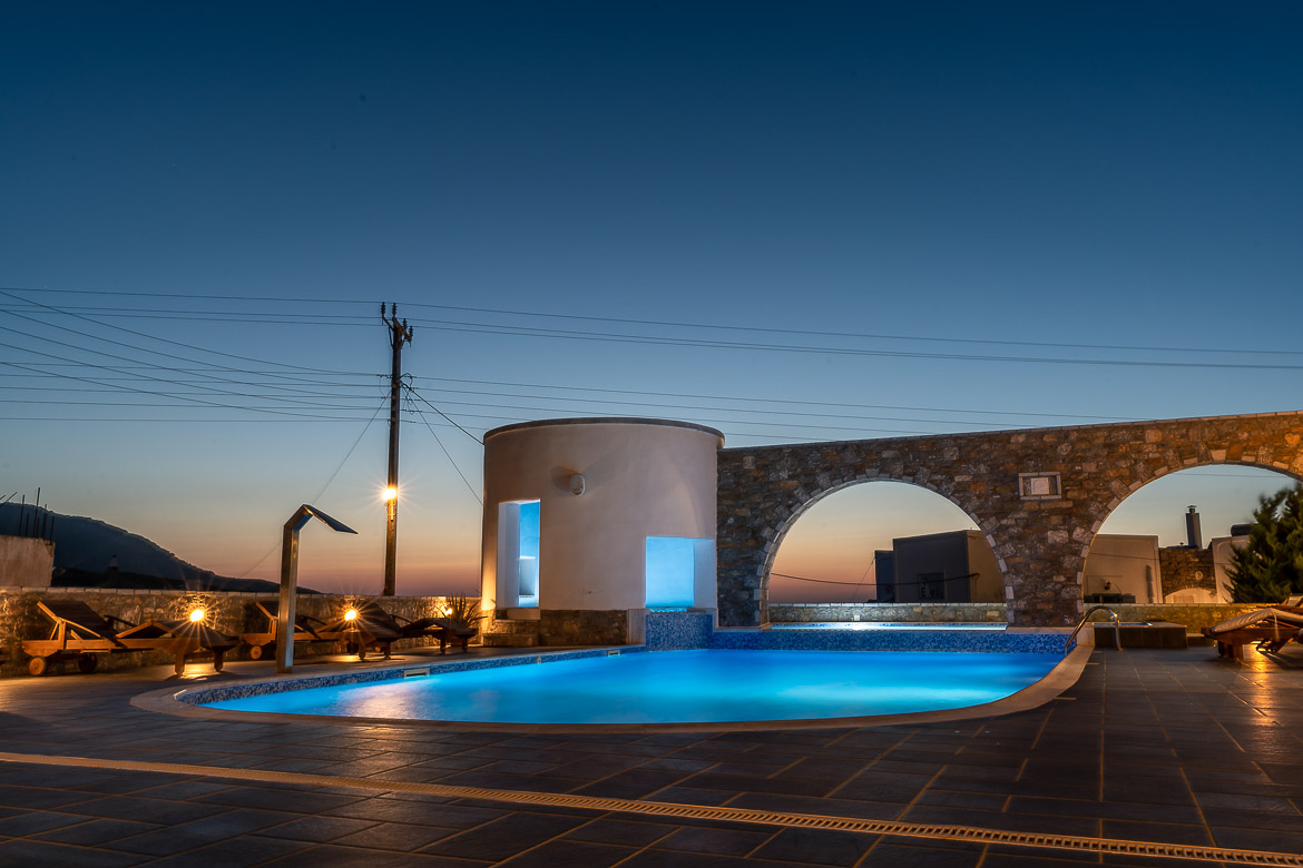 This image shows the swimming pool at Vigla Hotel Amorgos all lit up right after sunset.