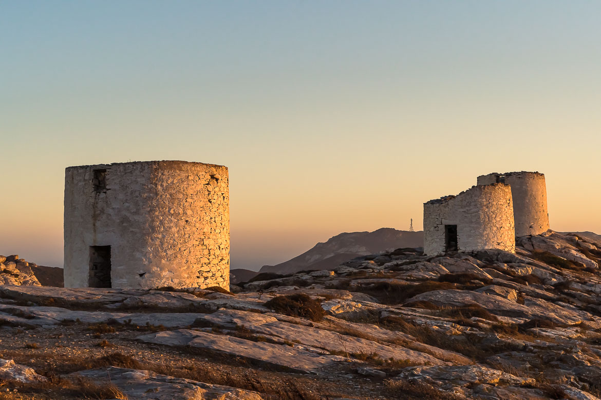 This image shows three windmills at the top of the hill doused in the golden light of the sunset.