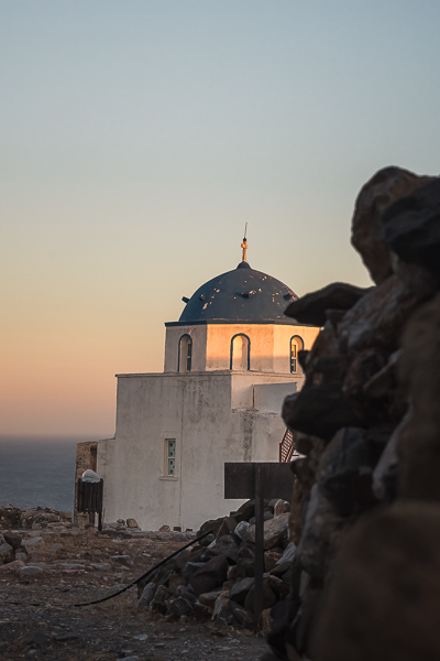 This image shows a whitewashed church with a blue dome among the ruins of Astypalaia Castle. In the background, the sea and the orange sky. Visiting the castle at sunset is one of the best things to do in Astypalaia.