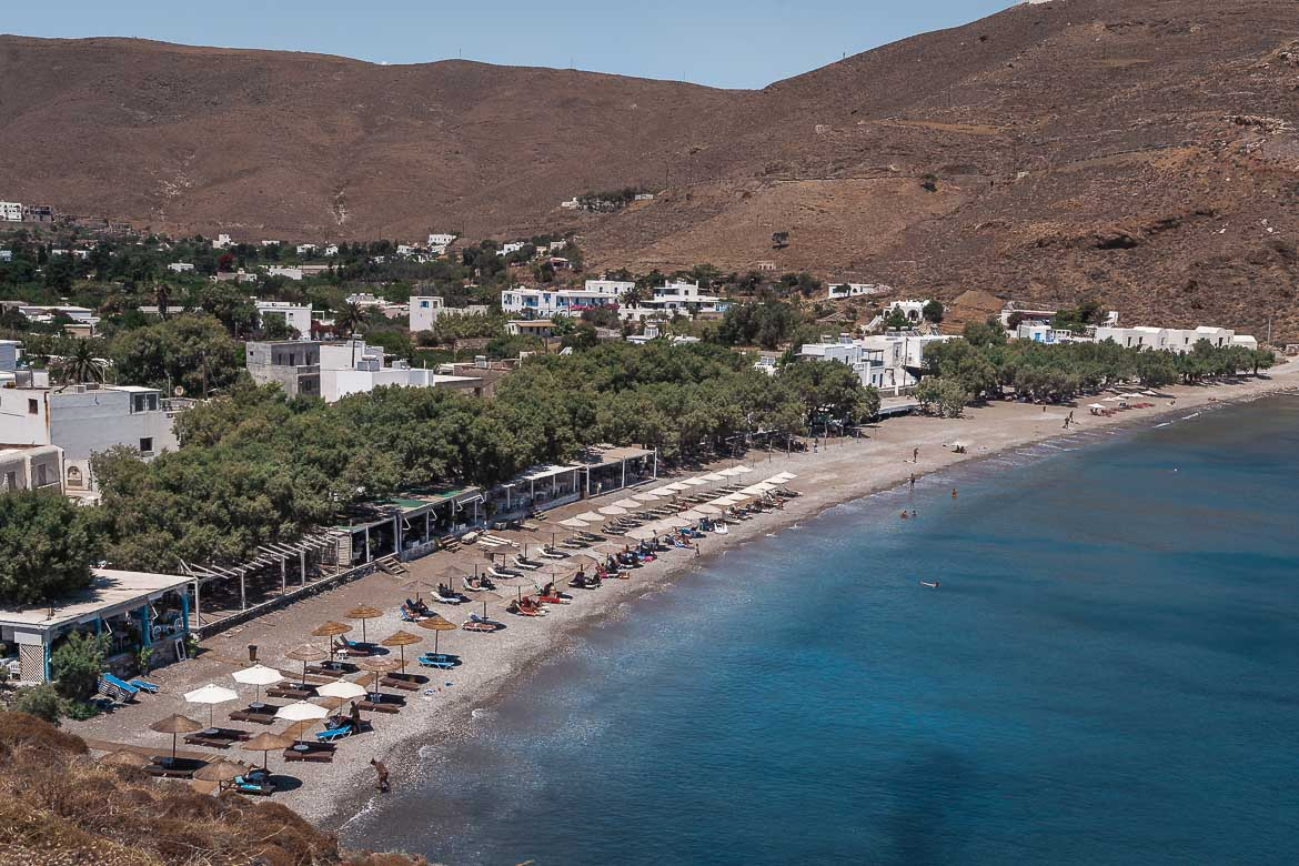 This is a panoramic shot of Livadi Beach. There are sunbeds and umbrellas, while many shops line the beachfront.