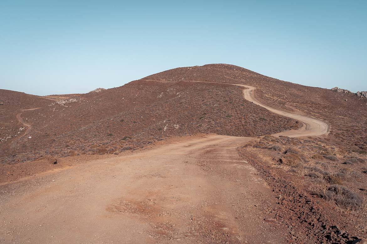 This image shows a barren landscape with a dirt road winding through it.