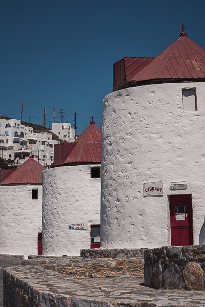 This is a close up of three of Astypalaia's restored windmills. They are whitewashed with red conical roofs.